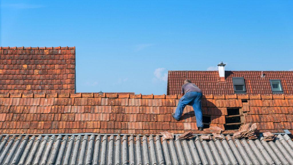 Auch im Notfall für Sie da - Dachdecker beim Flicken eines Loches im Dach